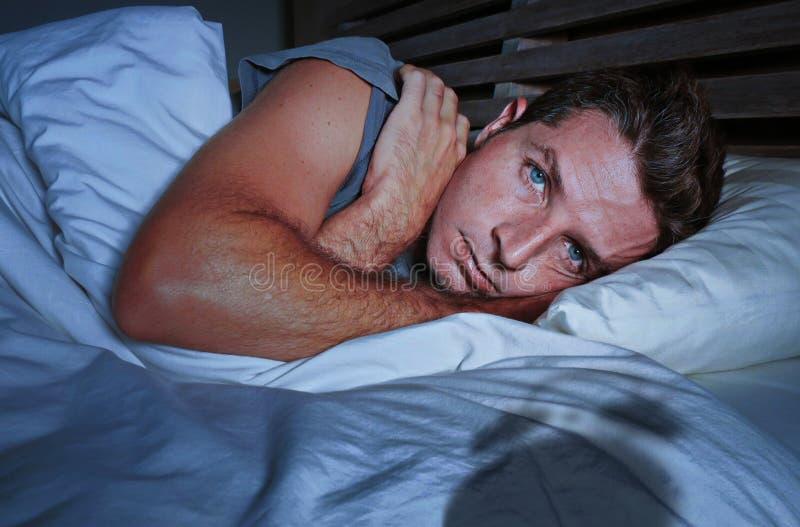 Rusteloze ongerust gemaakte jonge aantrekkelijke mens wakker bij nacht die op slapeloos bed liggen hebbend geopende ogen gedeprim royalty-vrije stock fotografie