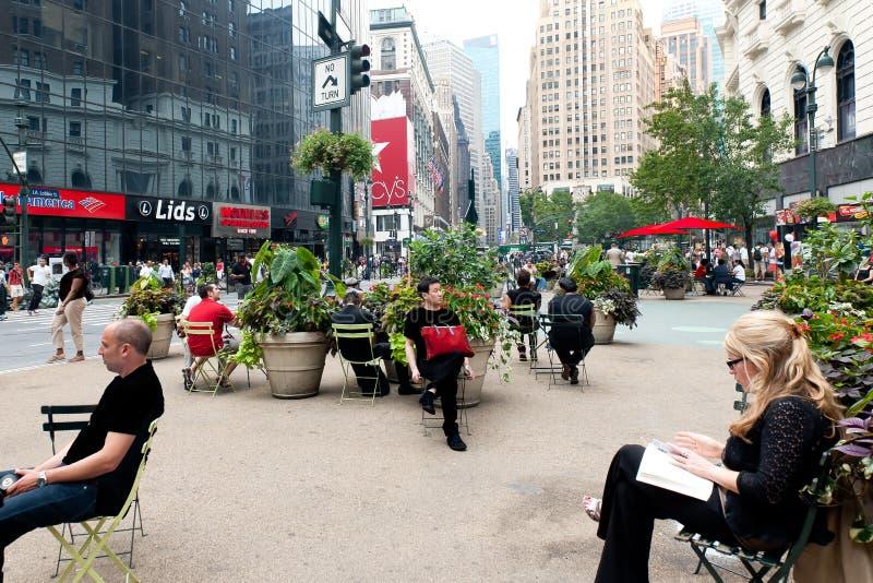 Rustend in midden van stroom van toeristen - het straatleven New York, Times Square stock fotografie
