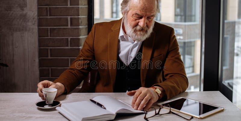 Rustende oude zakenman mannelijk drink thee op het werk stock foto