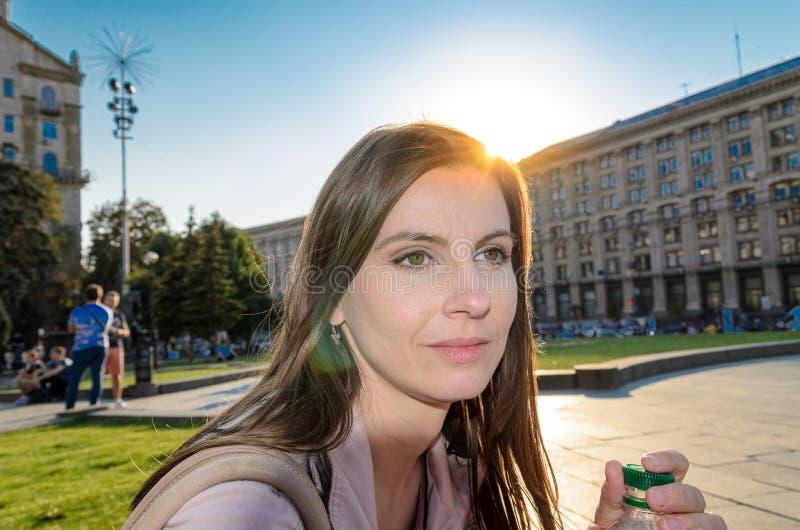 Rustende vrouw backlit door zon, cityscape op de achtergrond gelijk te maken royalty-vrije stock foto