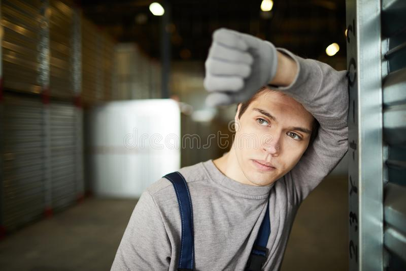 Rustgevende kerel die op ladingscontainer leunen stock afbeelding