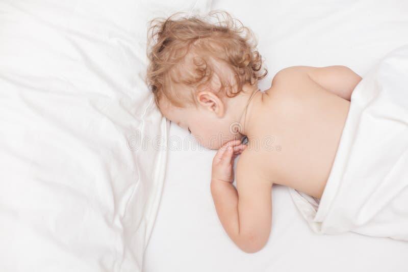 Rustgevende twee jaar de oude van het babymeisje slaap op bed royalty-vrije stock fotografie