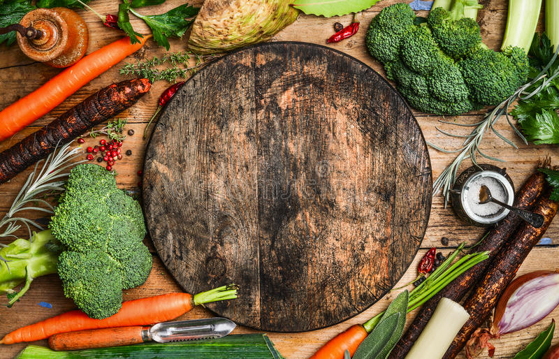 Rustic background with farm vegetables and blank round cutting board, top view royalty free stock photos