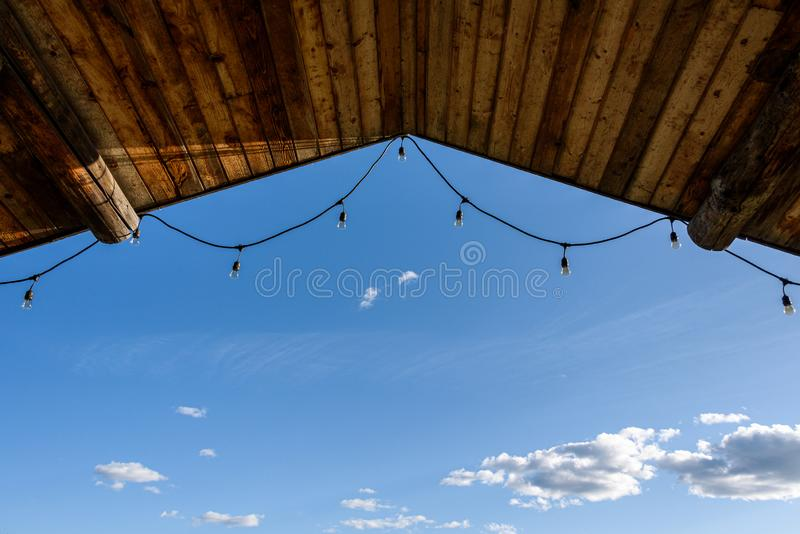 Rustic background of outdoor wood ceiling with log beams and string of lights framing a blue sky with white clouds stock images