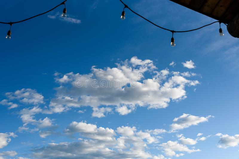 Rustic background of outdoor wood ceiling and string of lights framing a blue sky with white clouds royalty free stock photos