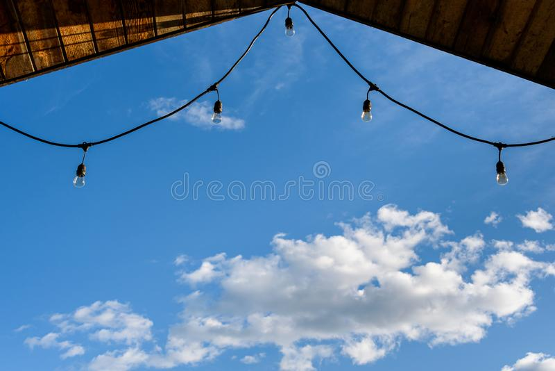 Rustic background of outdoor wood ceiling and string of lights framing a blue sky with white clouds stock photos