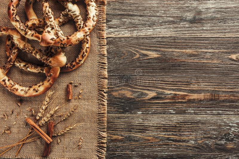 Rustic background, pretzels or bretzels and cinnamon sticks on wooden table. Concept of pastry, top view royalty free stock image