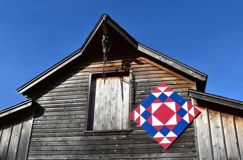 Rustic barn with an Amish quilt against a blue sky stock photo