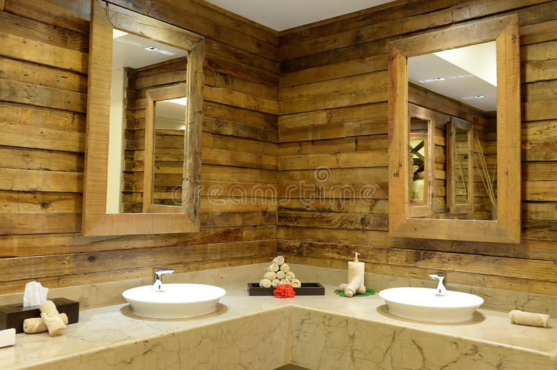Rustic bathroom interior. Rustic pine board walls inside bathroom with granite counter tops and porcelain sinks with mirrors royalty free stock photography