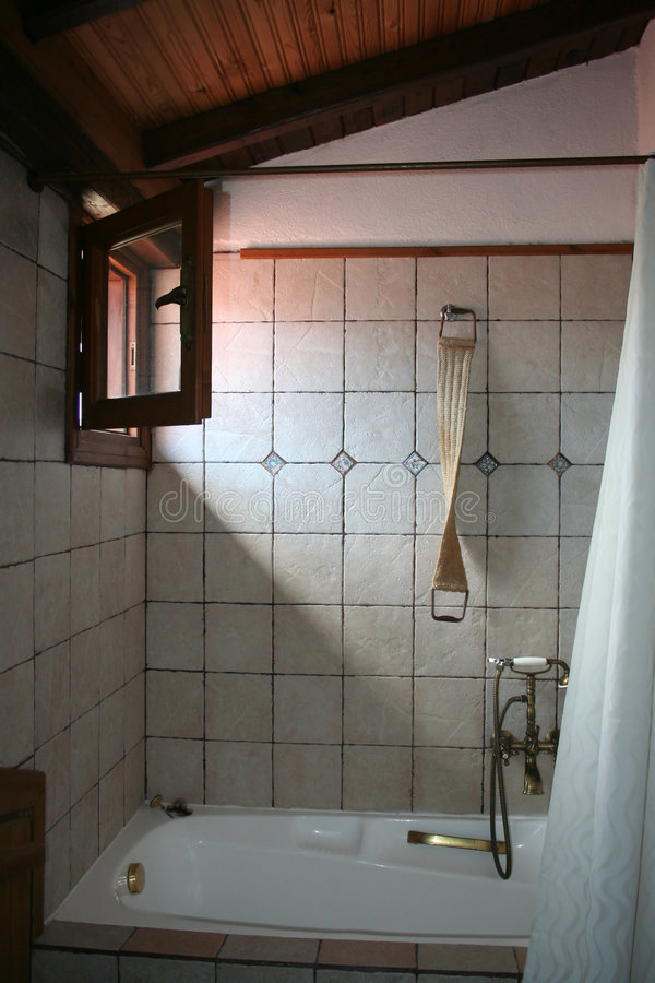Rustic bathroom lit by sunlight from open window stock images