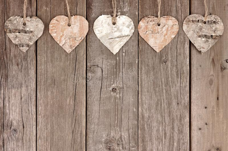 Rustic birch bark heart ornaments hanging against wood. Rustic birch bark heart ornaments hanging against a vintage wooden background royalty free stock photos