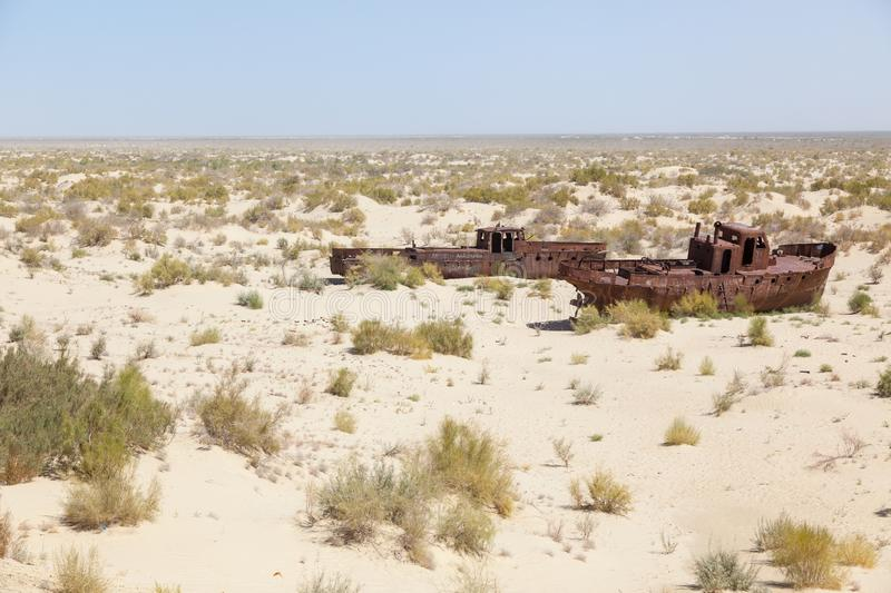 Rustic boats on a ship graveyards on a desert around Moynaq, Muynak or Moynoq - Aral sea or Aral lake - Uzbekistan in Central Asia. Rustic boats on a ship stock photo