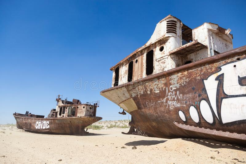 Rustic boats on a ship graveyards on a desert around Moynaq, Muynak or Moynoq - Aral sea or Aral lake - Uzbekistan in Central Asia. Rustic boats on a ship stock photos