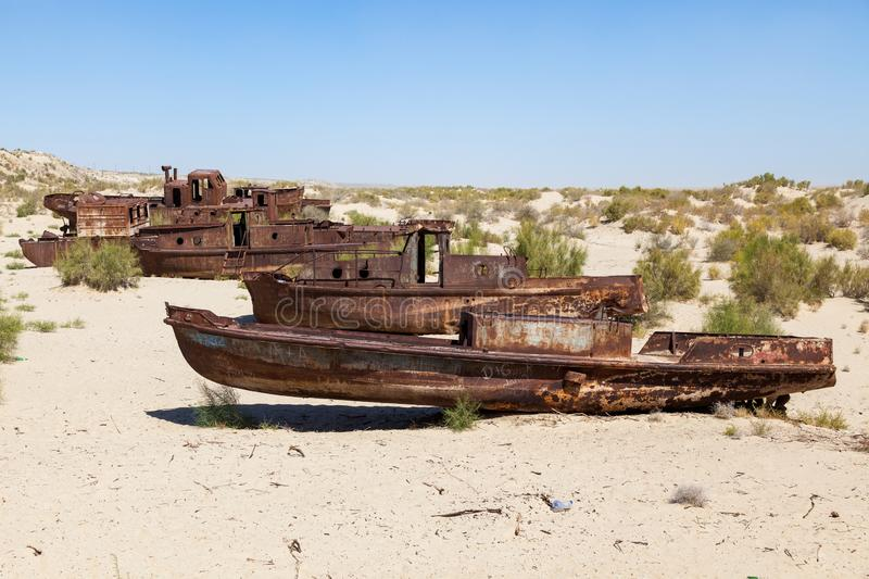 Rustic boats on a ship graveyards on a desert around Moynaq, Muynak or Moynoq - Aral sea or Aral lake - Uzbekistan in Central Asia. Rustic boats on a ship royalty free stock image