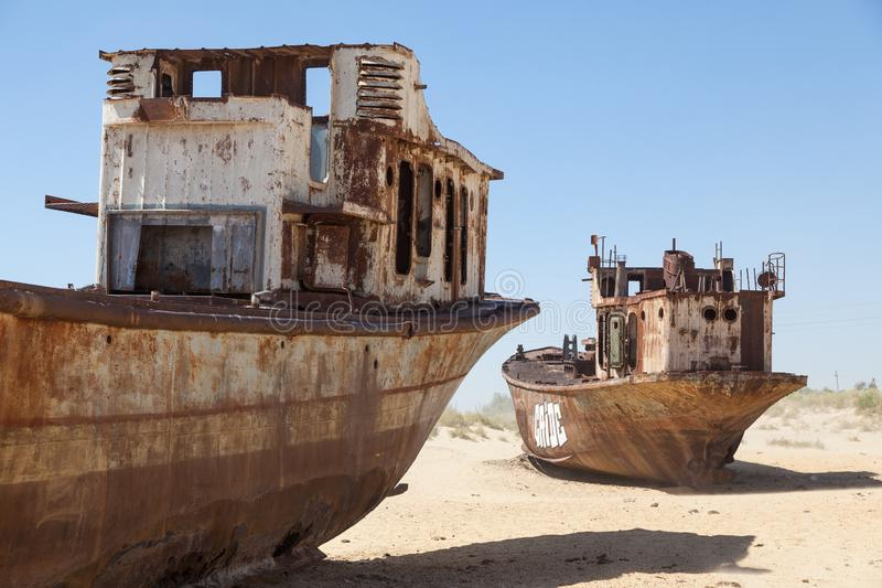 Rustic boats on a ship graveyards on a desert around Moynaq, Muynak or Moynoq - Aral sea or Aral lake - Uzbekistan in Central Asia. Rustic boats on a ship stock image