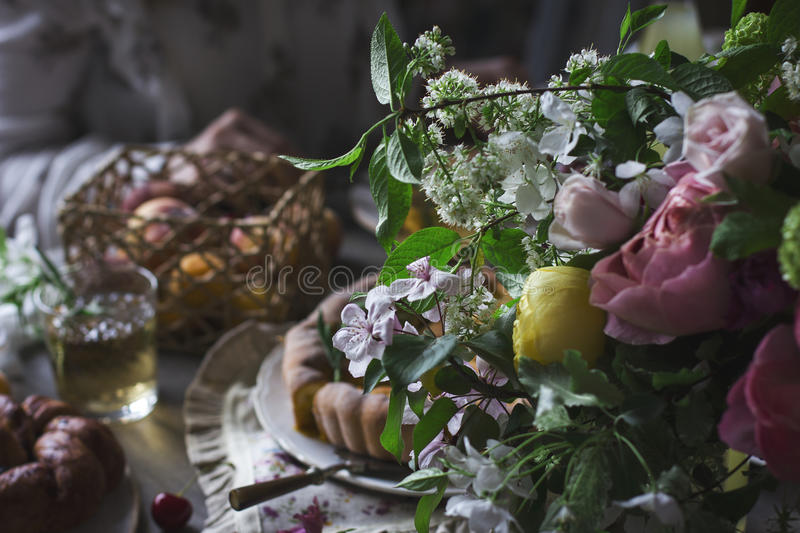 Rustic bouqet on the dining table. Bouquet of flowers in rustic style on the background of the dining table with food royalty free stock photography