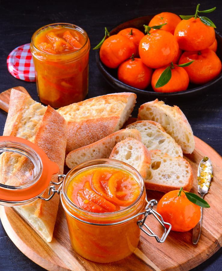 orange jam marmalade and rustic bread with oranges in background stock photo