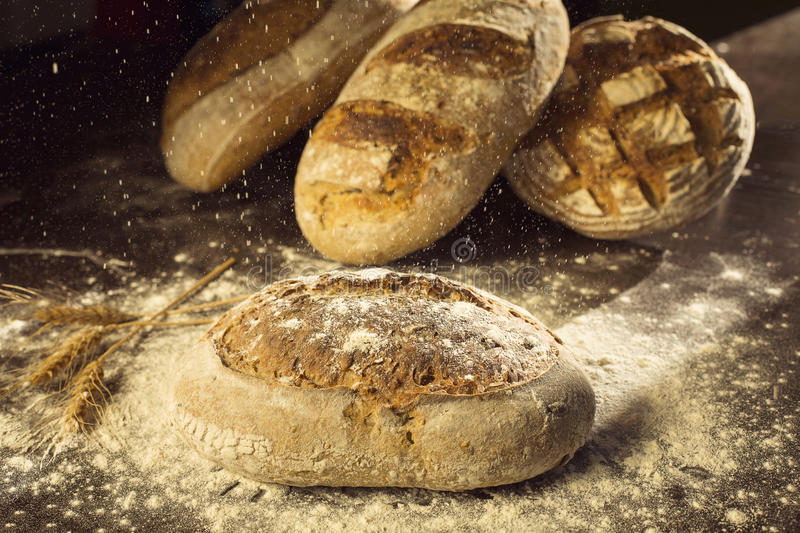 Rustic bread and wheat on black table with flour on it and poder royalty free stock images