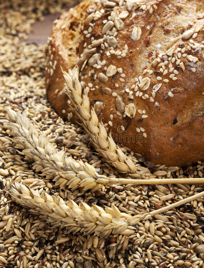 Rustic bread, wheat ears and grains stock photo