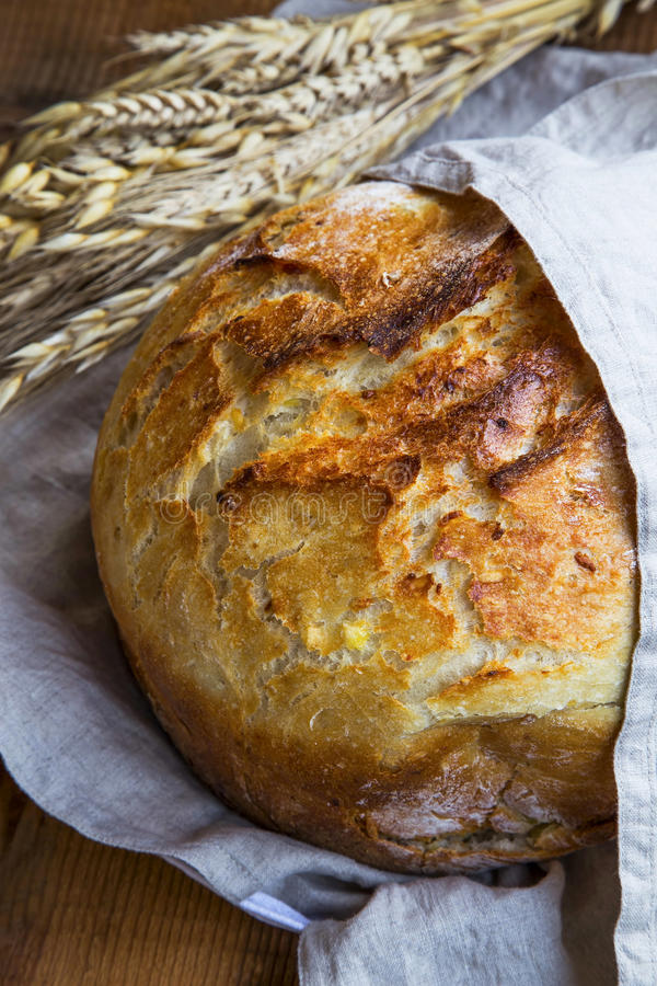 Rustic bread. Whole round bread with browned crust in linen towel and ears of wheat in the background royalty free stock photography