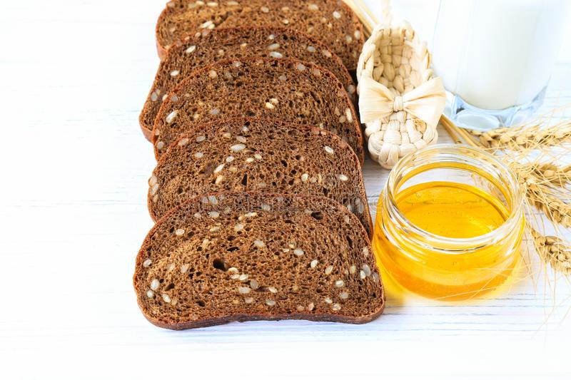 Rustic breakfast on a light wooden background - sliced bread with seeds, ears of wheat. straw wicker shoes. cup with honey royalty free stock photos