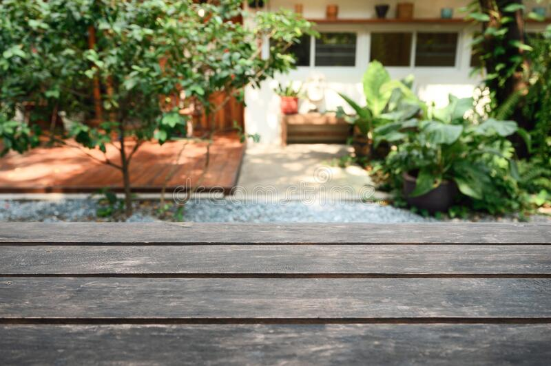 Rustic brown wooden table top on blurred green plant in garden backyard. On sunny royalty free stock image