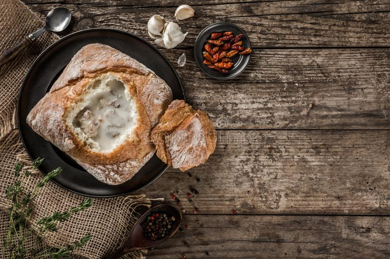 Rustic chicken soup with mushrooms in bread with spices on rustic wooden background. royalty free stock photo
