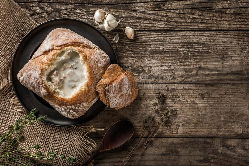 Rustic chicken soup with mushrooms in bread with spices on rustic wooden background. Healthy food concept, top view, flat lay,. Copy space royalty free stock images