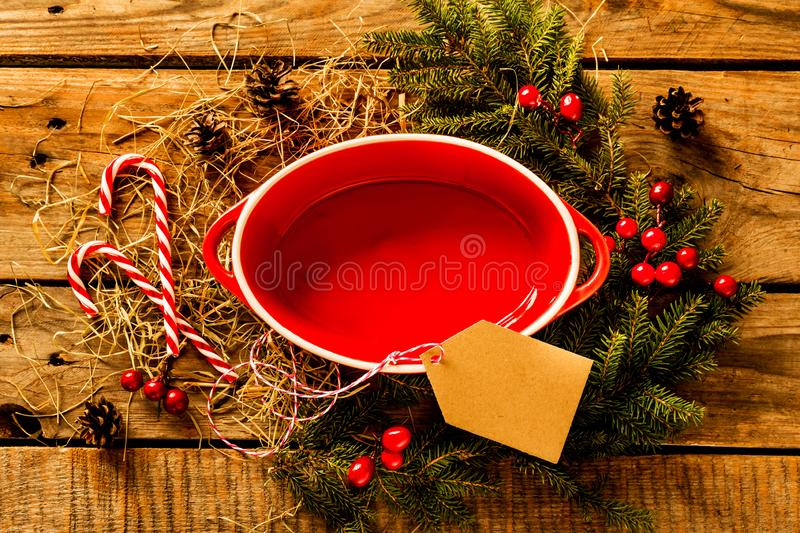 Rustic christmas background with red empty baking dish. Christmas background with red empty oval ceramic baking dish. Blank tag and rustic natural decorations on royalty free stock photography