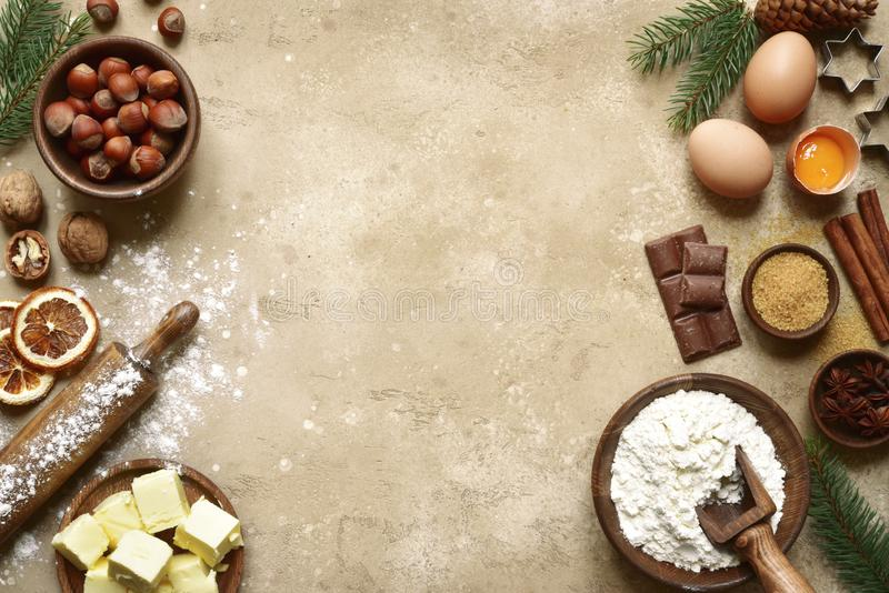 Rustic christmas baking background with ingredients for making c. Ookies or cake over beige slate,stone or concrete background.Top view with space for text royalty free stock photo