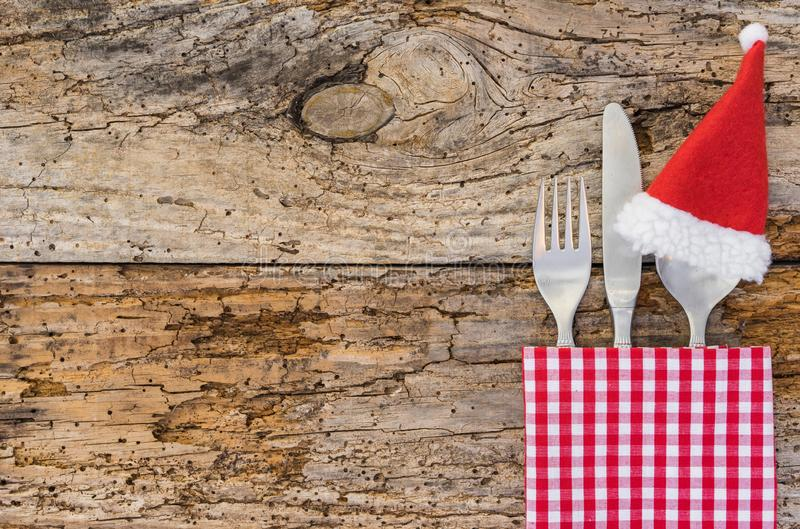 Rustic christmas dinner table place setting with santa claus hat and napkin on wood background stock photography