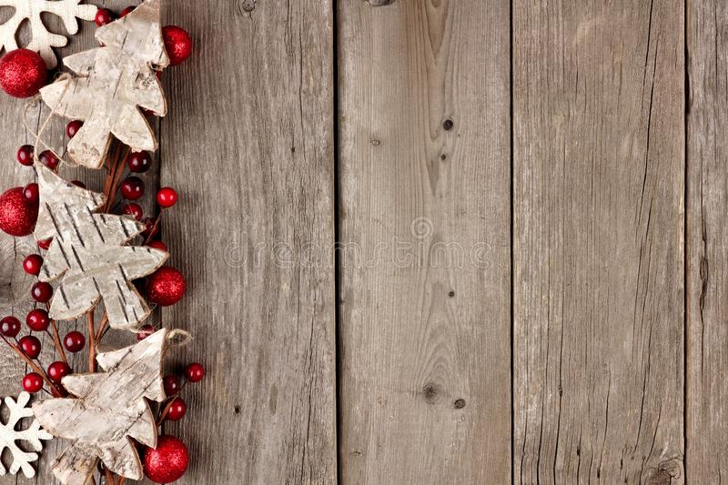 Rustic Christmas side border with wood ornaments and berries on aged wood stock photos