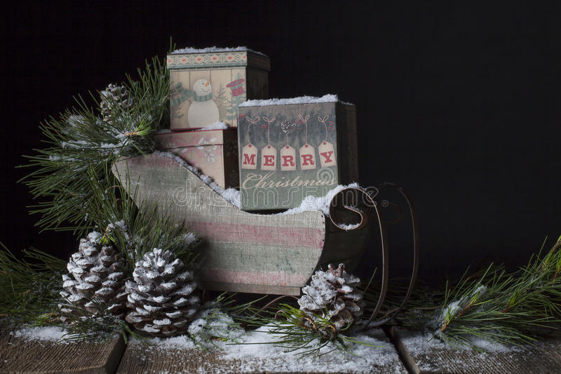 Rustic Christmas Sleigh. A rustic Christmas sleigh filled with vintage boxes, Merry Christmas printed on boxes along with cheerful snowman. sleigh surrounded royalty free stock photo