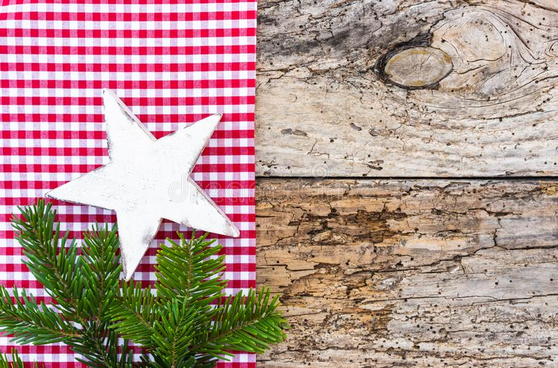Rustic Christmas star background with fir green branch and red checkered fabric background stock images