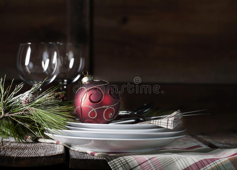 Rustic Christmas Table Setting. Stacked white plates with plaid dinner napkin, flatware and red christmas ornament on rustic table with natural pine bough and stock images