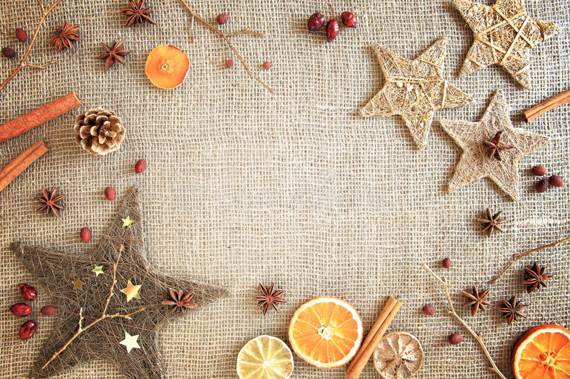 Rustic Christmas / winter border. Rustic Christmas border of seasons ingredients and decorations on a jute background. Central copy space royalty free stock image