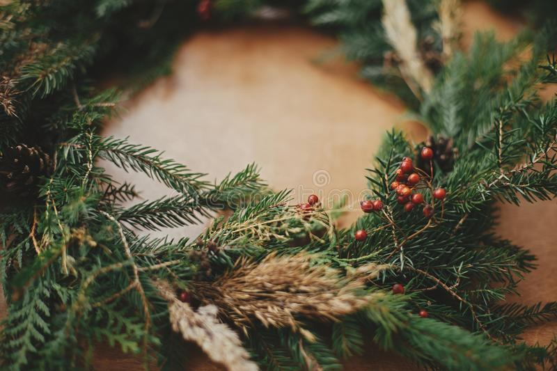Rustic Christmas wreath detail closeup. Fir branches, pine cones, berries on wooden table. Authentic stylish still life. Making. Christmas wreath royalty free stock photo