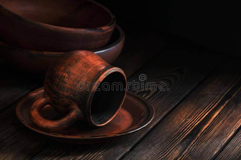 Rustic clay dishes on a wooden brown plank table. Selective focus. Food dark photo. Rustic clay crockery on a wooden brown plank table. Selective focus. Food royalty free stock photos