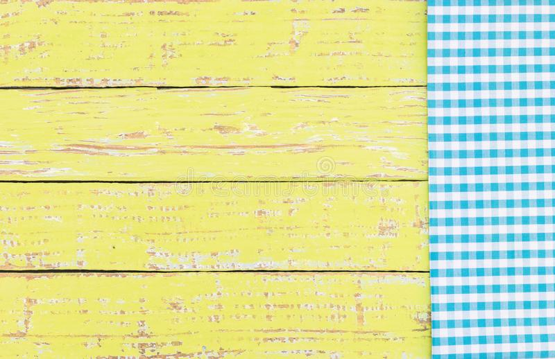 Rustic colored wood background texture with blue checked tablecloth. Yellow wooden table background rustic texture, with blue checkered tablecloth, high angel stock photos