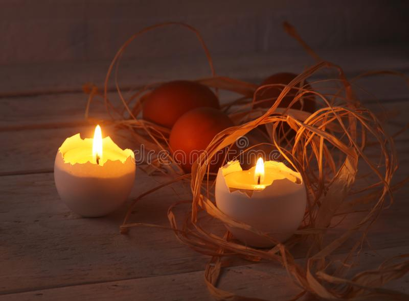 Rustic composition with candles and eggs. Happy easter. Selective focus. stock photo