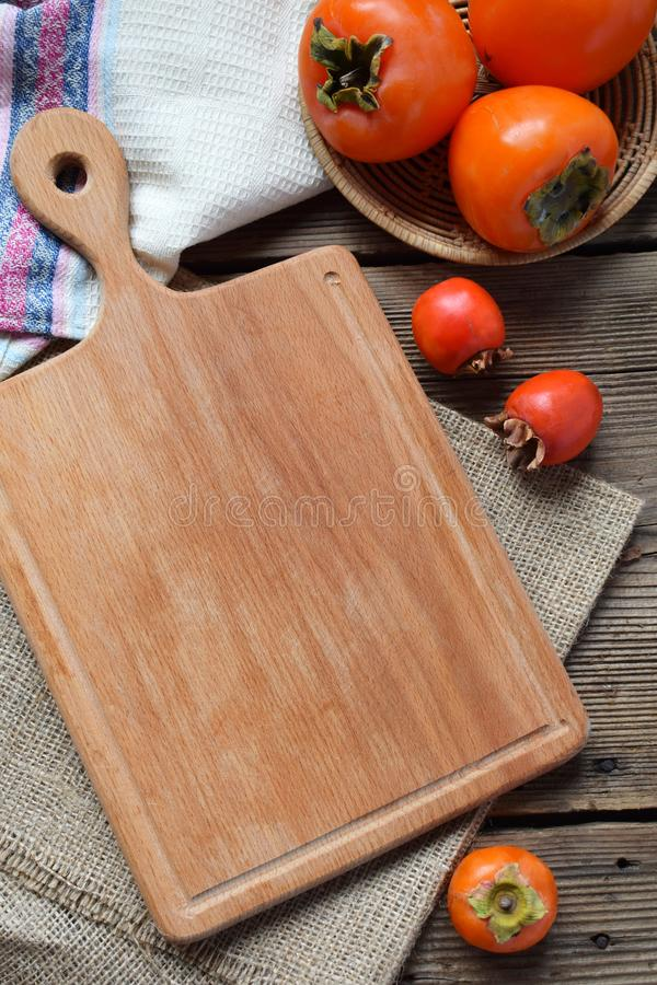 Rustic composition with different varieties of persimmons and wooden cutting board. Country style. Baking or cooking background. stock image