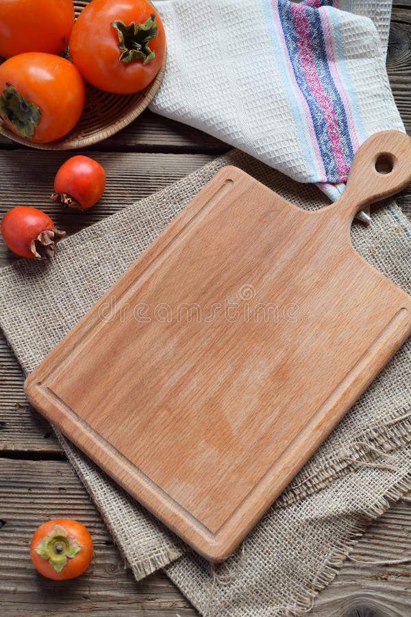 Rustic composition with different varieties of persimmons and wooden cutting board. Country style. Baking or cooking background. stock photo