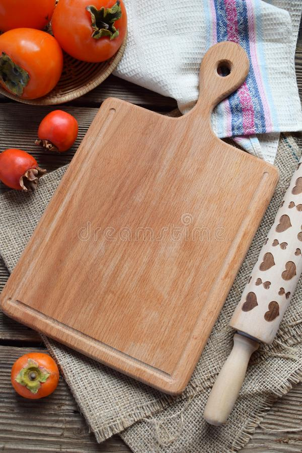 Rustic composition with different varieties of persimmons and wooden cutting board. Country style. Baking or cooking background. stock photography
