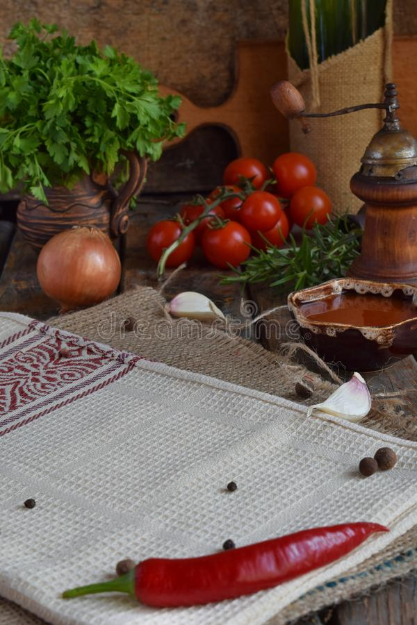 Rustic composition with pepper mill, tomato souce, bottles of wine, greens, vegetables and spices. Country style. Baking or cookin stock image