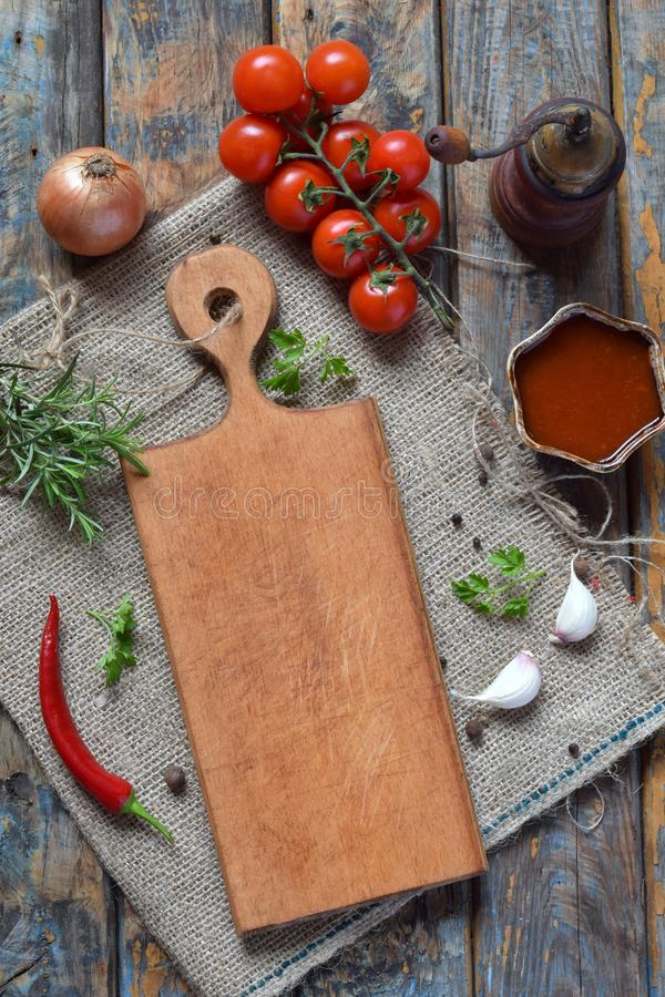 Rustic composition with wooden board, pepper mill, tomato souce, fresh herbs, vegetables and spices. Country style. Baking or cook royalty free stock images