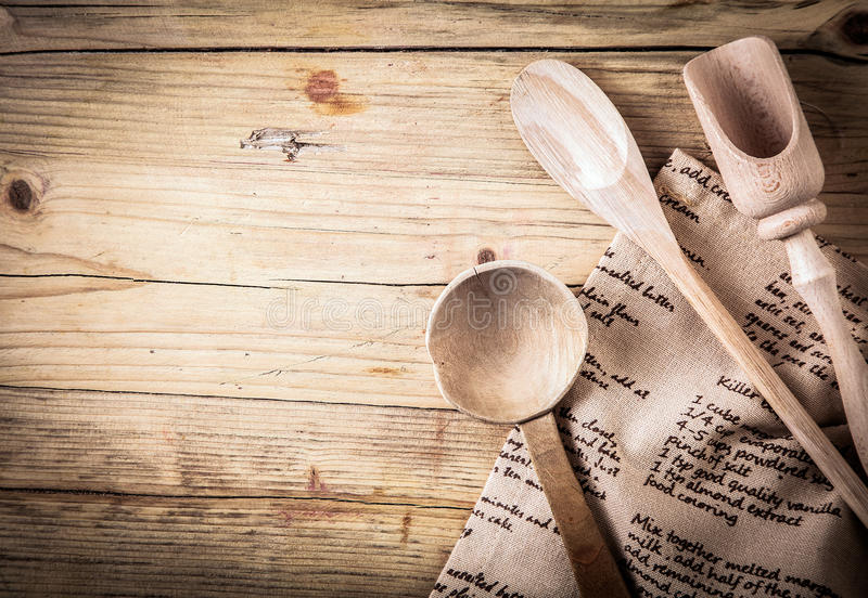 Rustic cooking utensils with a recipe. Rustic cooking utensils with a wooden spoon, ladle and scoop lying on a folded cloth with a recipe on it on an old cracked royalty free stock photo