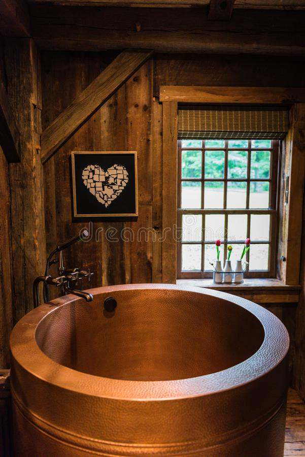 Rustic Copper Japanese Soaking Tub. Therapeutic copper Japanese soaking tub set in rustic bathroom in Hudson Valley country cottage royalty free stock photos