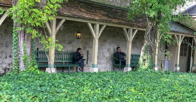 Rustic courtyard at Petit Trianon, Versailles, France. September 2017: Tourists relax in rustic covered courtyard near Petit Trianon, Versailles, France stock photos