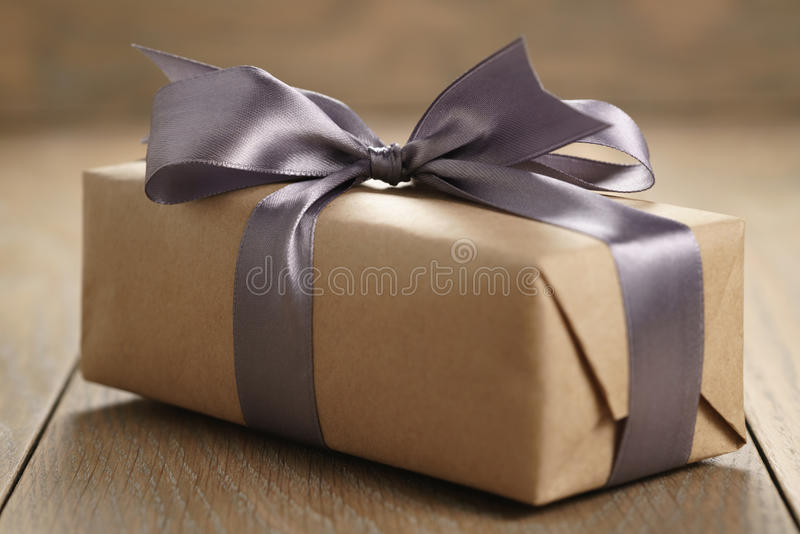 Rustic craft paper gift box with lilac ribbon bow on wood table stock photo
