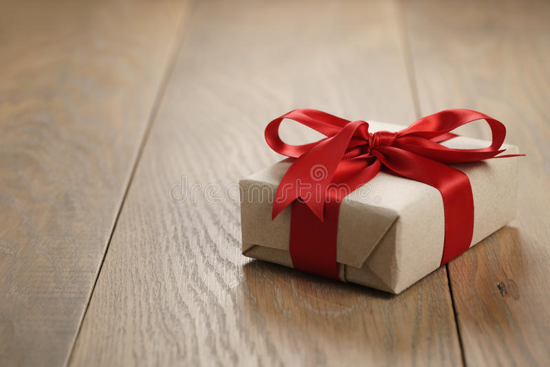 Rustic craft paper gift box with red ribbon bow on wood table. Shallow focus stock image